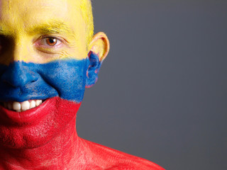 Man face painted with colombian flag, smiling expression