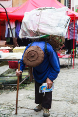 Old bended man walking with a basket on his back