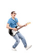 Full length portrait of a guy playing on an electric guitar