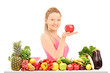 Female holding an apple and posing behind a table full of vegate