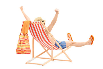 Happy young male on a beach chair gesturing happiness