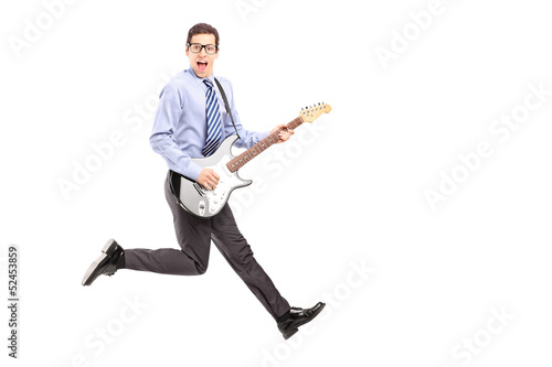 Full length portrait of energetic young male jumping with a guit