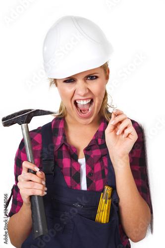 Junge Heimwerkerin mit Hammer schreit vor Angst