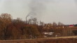 Air pollution by dark smoke coming out of two factory chimneys.