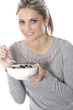 Model Released. Young Woman Eating Breakfast Cereal with Fruit