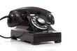 A retro black rotary phone on a white background