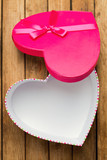 Open heart shape gift box over wooden background
