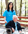 Kind Nurse With Elderly Lady In Wheelchair