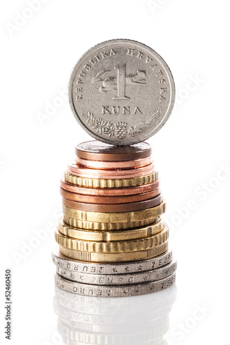 A standing 1 kuna coin - Croatian currency - on top of the stack