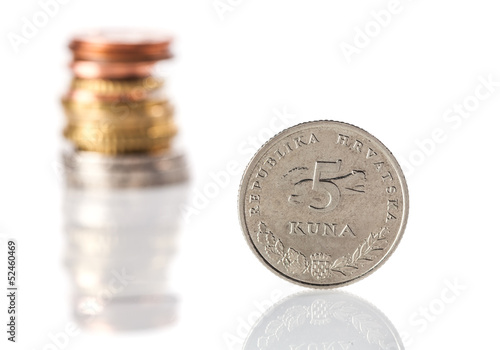 A standing 5 kuna coin - Croatian currency - in front of the sta