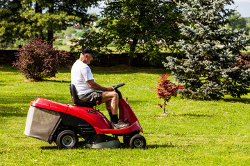 Senior man driving a red lawn mower (tractor)