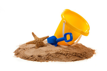 A yellow pail and blue shovel on the beach with a starfish