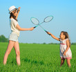 The young girls plays with a racket in badminton