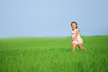 Young happy girl running at green wheat field