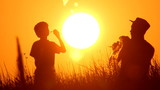 dad and son making soap bubbles in the nature, sunset,