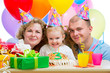 kid girl with parents blow candles on birthday cake