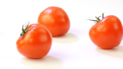 Ripe tomatoes close up on a white background
