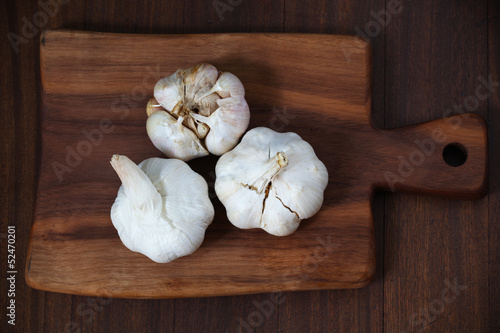 Three Garlic bulbs on the wooden cutting board