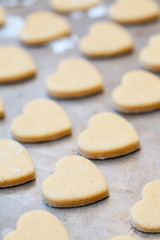 Unbaked heart shaped shortbread cookies on baking tray, selectiv