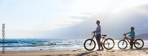 canvas print picture Mother and son biking at beach