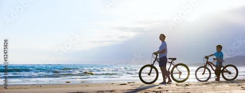 Leinwandbild Motiv Mother and son biking at beach