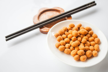 Peanuts snack coated with spicy seasoning and chopsticks