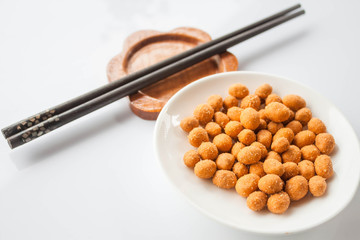 Spicy peanuts snack and chopsticks on white table