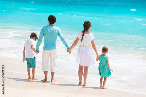 Family on a tropical beach vacation - 52478299
