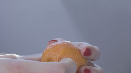 Hands of young woman peel tangerine (mandarin) with splashes