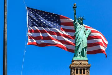 Freiheitsstatue vor Sternenbanner und blauem Himmel