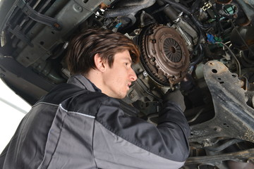 Auto Mechanic is working in car repair shop.