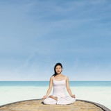 Meditating by lotus position in yoga