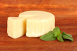 Cheese mozzarella and basil on wooden background