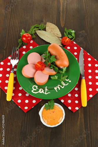 Sausage, greens, tomato on plate on wooden table