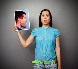 woman holding photo of aggressive man