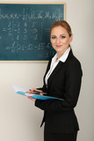 Portrait of teacher woman near the chalkboard in classroom