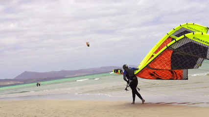 Kitesurfer walking on the beach with the kite, super slow motion