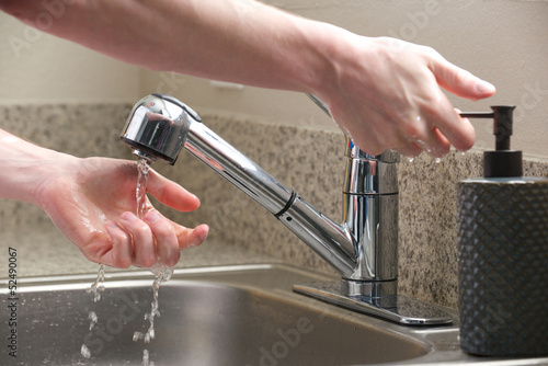 Hands reach for soap at the kitchen sink