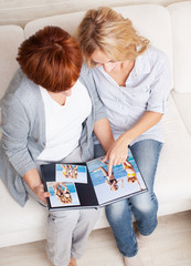 Mother and daughter looking photo book
