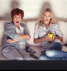 Mother with adult daughter watching television