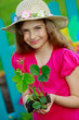 Gardening- lovely girl with strawberry seedling in the garden