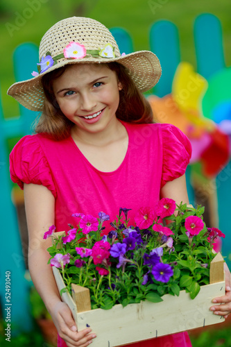 Gardening- lovely girl with petunia flowers in the garden