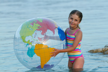 Lovely girl playing in the sea with  inflatable globe ball.