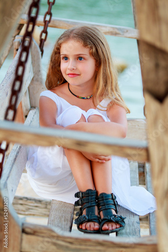 Lovely girl on bench in the beach resort