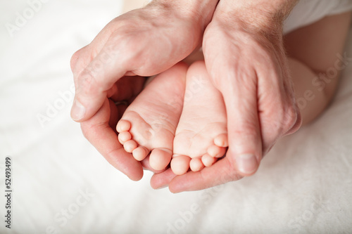 Tiny newborn baby`s feet in male hand