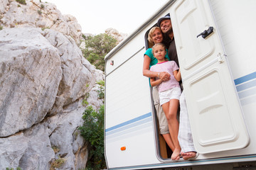 Holiday travel - family in caravan on camping