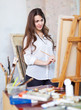 Long-haired girl paints with oil colors