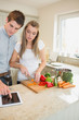 Couple looking at tablet pc while cooking