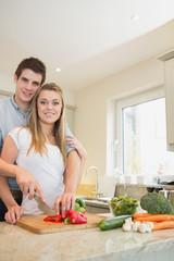 Happy couple preparing vegetables