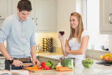 Man cutting vegetables with woman drinking wine